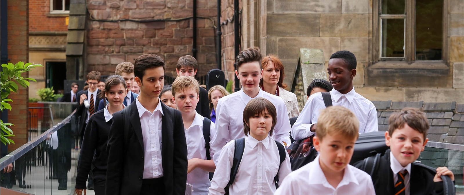 A large group of students crosses the bridge on Chetham's site